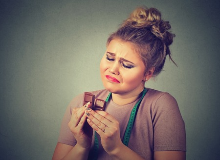 good and bad: Portrait sad young woman with measuring tape tired of diet restrictions craving sweets chocolate isolated on gray wall background. Human face expression emotion. Nutrition concept. Feeling of guilt Stock Photo