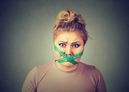cravings: Diet restriction and stress concept. Portrait of young frustrated woman with a green measuring tape around her mouth isolated on gray wall background. Face expression emotion