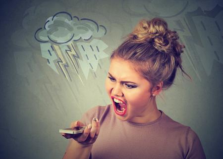mujer decepcionada: Retrato enojado joven gritando en el teléfono móvil aislado en el fondo de la pared gris. Negativas emociones humanas sentimientos Foto de archivo