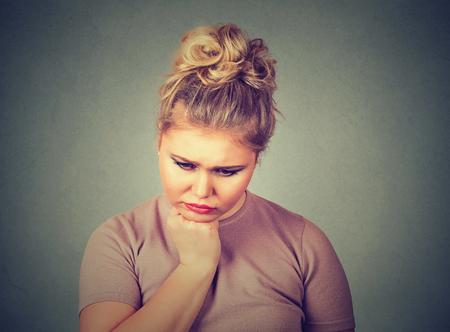 Close-up portret ongelukkig overgewicht vrouw depressief kijken naar beneden geïsoleerd op grijze muur achtergrond. Menselijke gezichtsuitdrukking emotie gevoelens