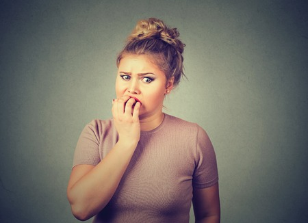Closeup portrait nervous stressed young woman student biting fingernails looking anxiously craving something isolated on gray wall background. Human emotion face expression feeling reaction