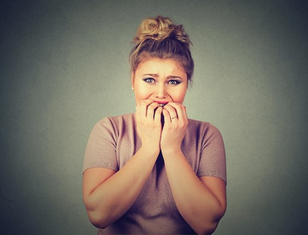Closeup portrait nervous stressed young woman student biting fingernails looking anxiously craving something isolated on gray wall background. Human emotion face expression feeling reaction Фото со стока - 58112217