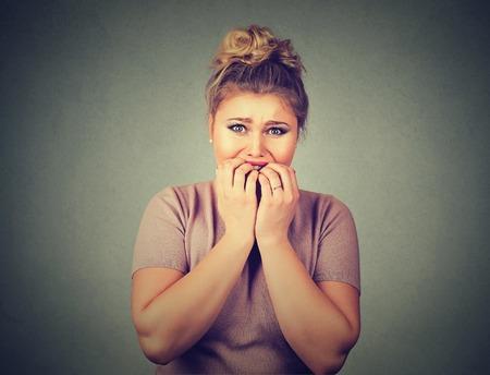 portrait Gros plan nerveux souligné jeune femme étudiant ongles mordre regardant avec anxiété envie quelque chose d'isolé sur gris fond mur. visage émotion humaine réaction de sentiment d'expression Banque d'images
