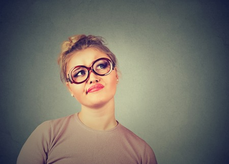 Closeup funny confused skeptical woman in glasses thinking planning looking up isolated on gray wall background copy space above head. Human face expression emotion feeling body language, perception Imagens