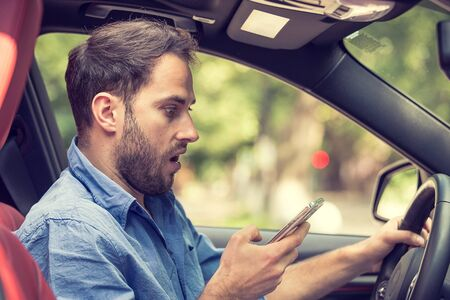 upset: Man sitting in car with mobile phone in hand texting while driving. Distracted shocked guy checking his smart phone not paying attention at road annoyed by bad text message email outdoors background Stock Photo