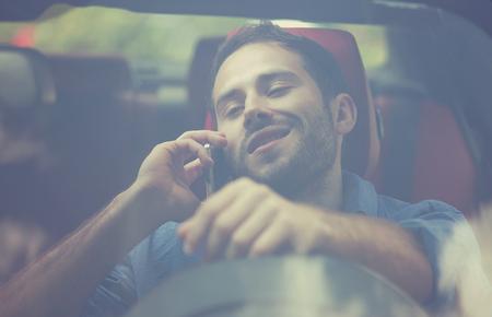 bad habits: apuesto joven vista de la ventana frontal hablando por teléfono móvil mientras conduce su coche. Arriesgadas, conductor imprudente malos hábitos. regla de la seguridad del tráfico violación falta de atención concepto