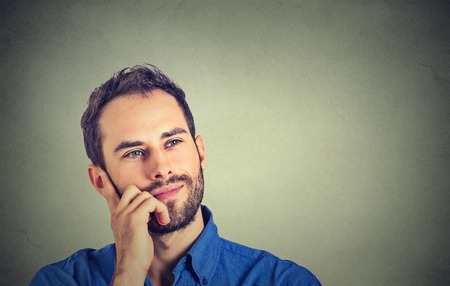 guys: Happy young man thinking daydreaming looking up isolated on gray wall background