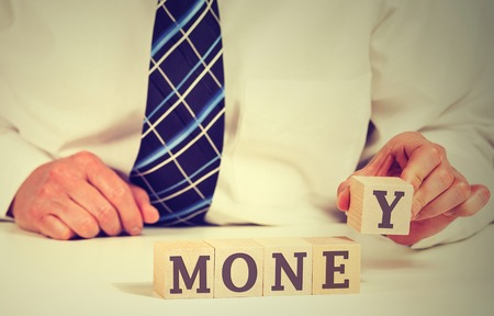 commercialism: Financial market concept. Businessman hands arranging small wooden blocks with word money