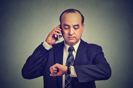 business for the middle: Business and time management concept. Middle aged  business man looking at wrist watch, talking on mobile phone running late for meeting. Time is money