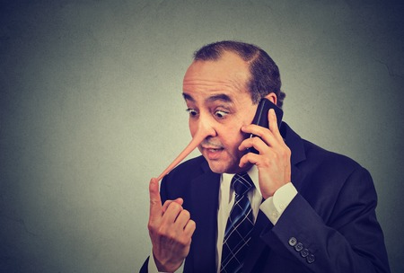 character traits: Liar customer service representative. Middle aged man with long nose talking on mobile phone lying isolated gray wall background. Liar concept. Human face expression emotion feeling character traits Stock Photo