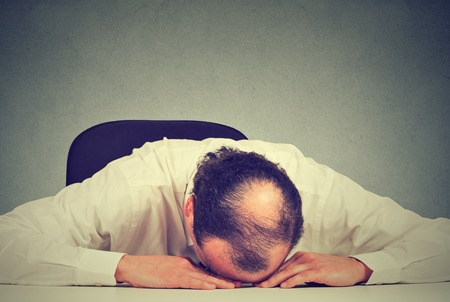 working hours: Closeup portrait, tired middle aged bald boss company employee sleeping after long working hours, resting on desk, isolated gray office wall background. Exhausting work hours Stock Photo
