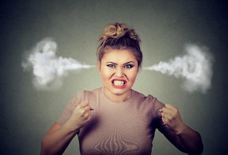 Primer enojado del retrato de la mujer joven que sopla vapor que sale de las orejas, a punto de tener nervioso desglose atómica gritando fondo negro aislado. actitud cara emoción expresión sentimiento humano negativo