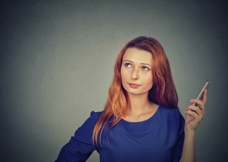 bored woman: Portrait of an annoyed and frustrated young woman on the phone isolated on gray wall background. Human emotion face expression feeling