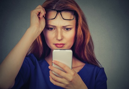 degeneration: Closeup portrait headshot young woman with glasses having trouble seeing cell phone has vision problems. Bad text message. Negative human emotion facial expression perception. Confusing technology