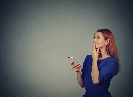 on the handphone: Beautiful woman texting on her mobile phone looking up planning isolated on gray wall background with copy space