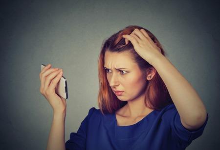 若い女性を驚かせたクローズ アップ不幸なイライラ動揺彼女は後退生え際の髪を失っています。灰色の背景。人間の顔の表現感情。美容ヘアスタイ