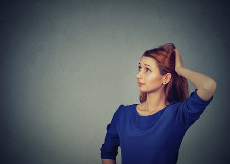 Contused thinking woman bewildered scratching her head seeks a solution isolated on gray wall background with blank copy space. Young woman looking up
