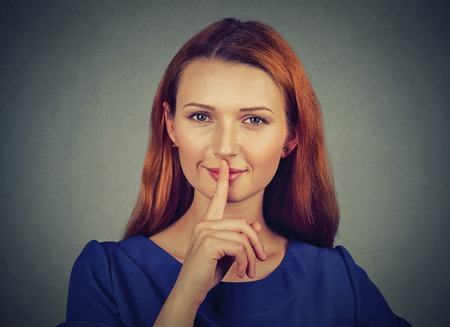 hearsay: Closeup portrait secretive young woman placing finger on lips asking shh, quiet, silence looking at camera isolated gray background. Human face expressions, sign emotion feeling body language reaction