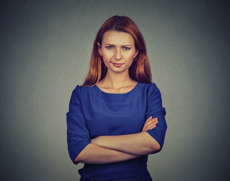 Closeup portrait of angry young woman, being skeptical, displeased isolated on gray wall background. Negative human emotions facial expression feelings attitude Stock Photo