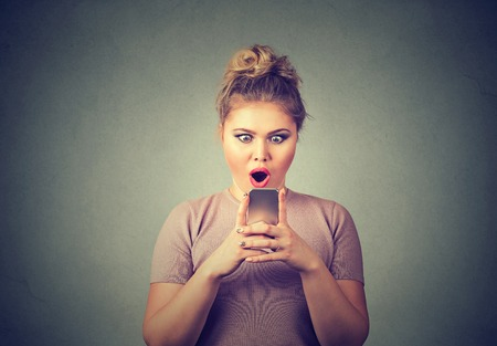 bad girl: Closeup portrait anxious amazed young girl looking at phone seeing bad news or photos with disgusting emotion on her face isolated on gray wall background. Human emotion, reaction, expression Stock Photo