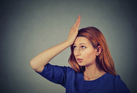 err: Regrets wrong doing. Closeup portrait silly young woman, slapping hand on head having duh moment isolated on gray background. Negative human emotion facial expression feeling, body language, reaction