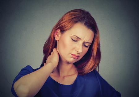 Powrót i choroby kręgosłupa. Zbliżenie portret zmęczony kobieta masuje jej bolesne szyi samodzielnie na szarym tle ściany. wyraz ludzkiej twarzy. Przewlekła choroba zmęczenie