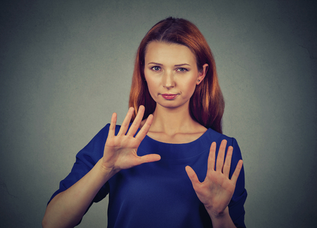 bad attitude: Closeup portrait young annoyed angry woman with bad attitude gesturing with palms outward to stop isolated on gray wall background. Negative human emotion face expression feeling body language