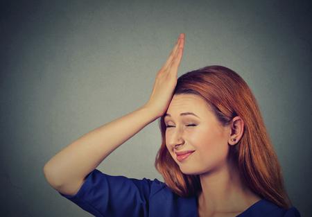 Bedauert, falsch zu machen. Nahaufnahmeportrait dumme junge Frau, Hand auf den Kopf mit duh Moment auf grauem Hintergrund schlagend. Negative menschliche Emotionen Mimik Gefühl, Körpersprache, Reaktion Standard-Bild