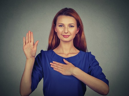 testify: Young woman making a promise isolated on gray wall background