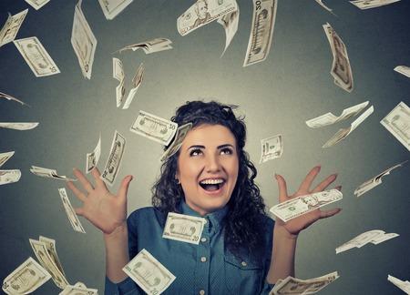 Porträt glückliche junge Frau jubelt Pumpen Fäusten feiert ekstatisch Erfolg unter einem Geld regen unten fallen Banknoten Dollar-Scheine, isoliert auf grau Wand Hintergrund mit Kopie Raum