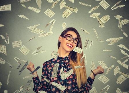 Retrato de la mujer joven feliz se regocija puños de bombeo de éxtasis celebra el éxito bajo una lluvia de dinero cayendo billetes de dólares billetes aislados sobre fondo gris de la pared con el espacio de la copia