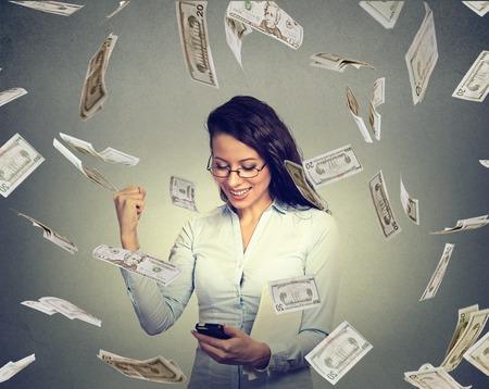 Jeune femme utilisant un téléphone intelligent construire des affaires en ligne faire des factures d'argent en dollars tomber. entrepreneur IT Débutant sous cash pluie. Succès concept d'économie bancaire Banque d'images