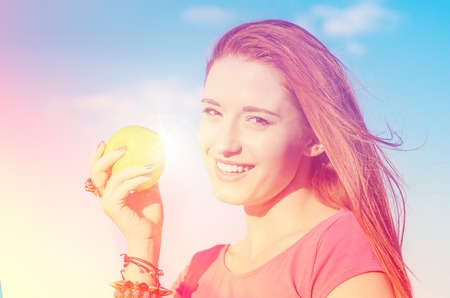 Portrait happy woman with green apple smiling enjoying good weather sunny summer day by the sea
