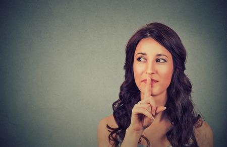 Ritratto di un'adolescente attraente con il dito sulle labbra, isolato su sfondo grigio muro concetto di studente spettacolo tranquillo, silenzio, gesto segreto, giovane donna bella bruna