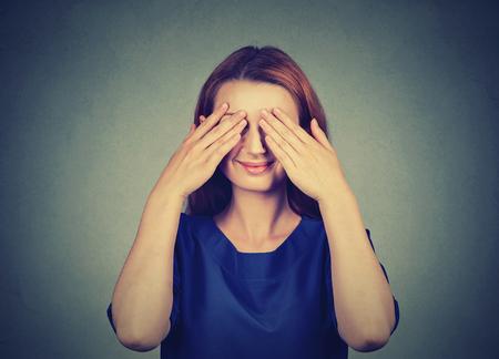 Verstecken. Lächelnde schüchterne Frau, die ihre Augen bedeckt Standard-Bild