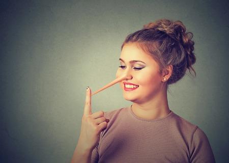 Concepto de mentiroso. Mujer feliz con nariz larga aislada sobre fondo de pared gris. Expresiones de rostro humano, emociones, sentimientos.