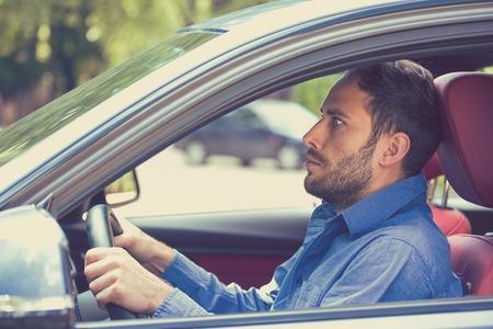 Angst lustig aussehender junger Mann Fahrer im Auto. Menschliche Emotionen Gesichtsausdruck. Seitenfenster Blick auf unerfahrene ängstlich motorist Standard-Bild