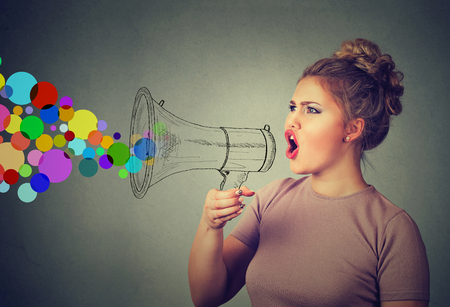 spread: Portrait young woman holding screaming in megaphone isolated on gray wall background. Negative face expression emotion feelings. Propaganda, breaking news, power, social media communication concept Stock Photo