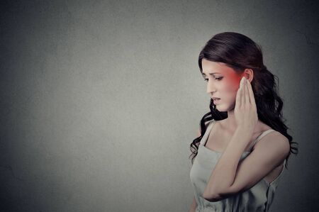 neuralgia: Tinnitus. Closeup up side profile sick female having ear pain touching her painful head temple colored in red isolated on gray wall background with blank copy space