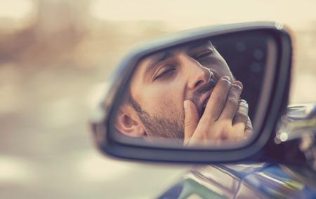 사이드 미러보기 반사 졸린 피곤 하 고 피로 하 고 지친 된 젊은이 긴 시간 드라이브 후 트래픽에서 그의 차를 운전. 교통 수면 부족 사고 개념 스톡 콘텐츠