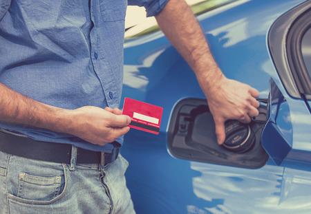 그의 새 차의 신용 카드 열기 연료 탱크와 남자