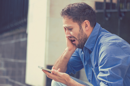 Desperate sad handsome young man looking at bad text message on his mobile phone sitting outside corporate office on a summer day. Human emotions reaction