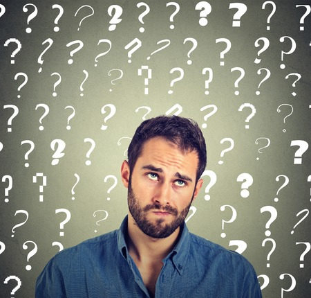 Confused skeptical man thinking looking up puzzled many question marks above head isolated on gray wall background. Human face expressions, emotions, feelings, body language. Funny young guy