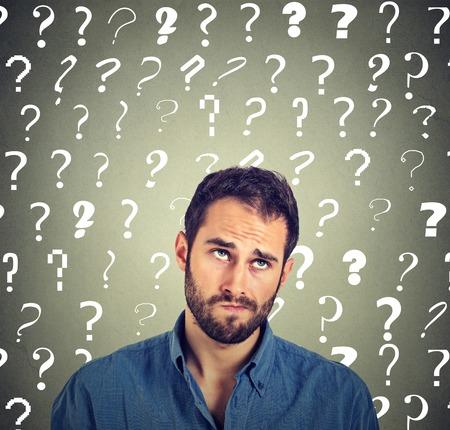 hombre escéptico confundido pensando en buscar desconcertado a muchos signos de interrogación sobre la cabeza aisladas sobre fondo gris de la pared. expresiones faciales humanas, las emociones, los sentimientos, el lenguaje corporal. chico joven divertida