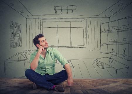homme Dreaming isolé sur étiré salon fond. Jeune homme pensée beau de fournir son nouvel appartement. Banque d'images