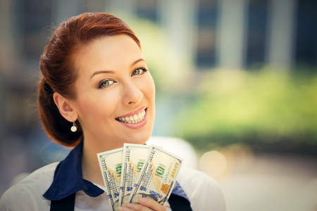 Closeup portrait happy excited successful young business woman holding money dollar bills in hand looking at camera isolated outdoors background. Positive emotion facial expression. Financial reward