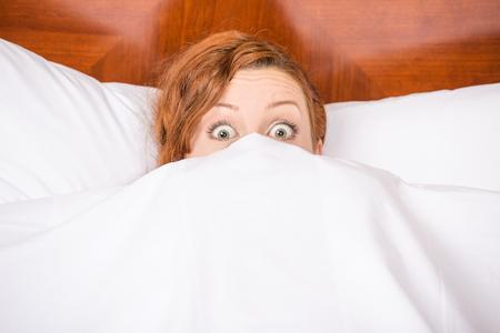 despertarse: mujer morena joven divertida en la cama que mira y mira a escondidas sobre hojas de sorpresa