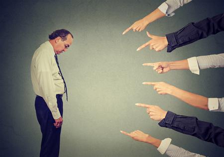 Concept van beschuldiging schuldige man. Zijprofiel triest boos man naar beneden te kijken vele vingers wijzen naar hem geïsoleerd grijs kantoor muur achtergrond. Negatieve menselijk gezicht expressie emotie gevoel