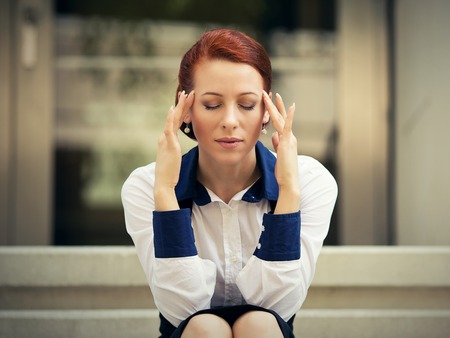 mindfulness: portrait stressed sad young woman sitting outdoors having headache. City urban life style stress Stock Photo