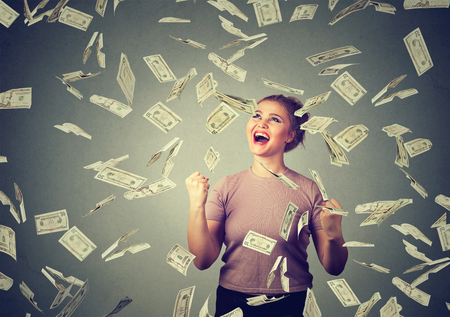 earn money: Portrait happy young woman exults pumping fists ecstatic celebrates success under a money rain falling down dollar bills banknotes isolated on gray wall background with copy space